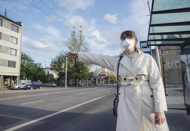Mulher usando máscara facial na cidade saudando um táxi — Fotografia de Stock
