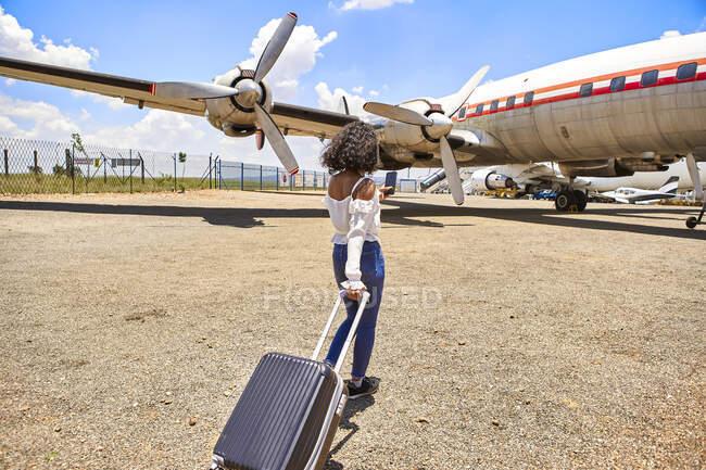 Vista posteriore della giovane donna che tira i bagagli mentre cammina verso l'aereo in aeroporto nella giornata di sole — Foto stock