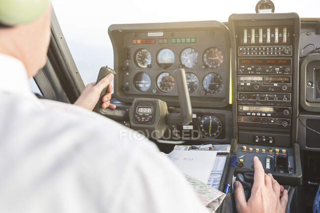 Pilot flying in sports plane, VFR chart on his lap — Stock Photo