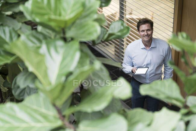 Бізнесмен стоїть у стійкому офісному будинку, тримаючи цифрову табличку. — стокове фото