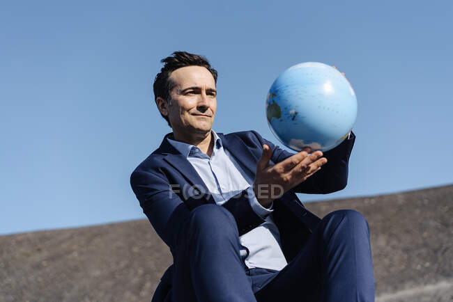 Зрелый бизнесмен держит глобус на заброшенной шахте — стоковое фото