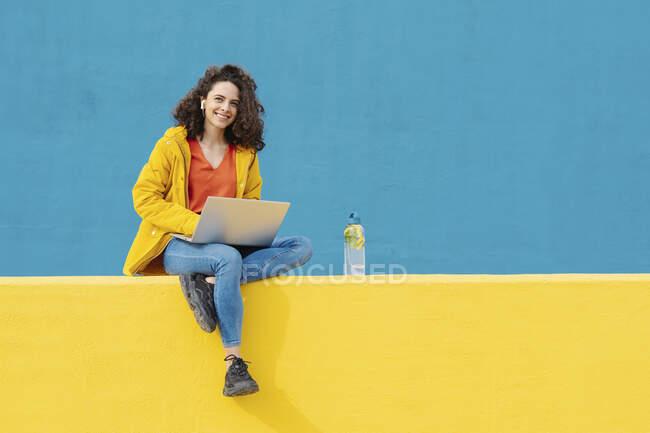 Retrato de una joven sonriente con auriculares y portátil sentado en la pared amarilla - foto de stock