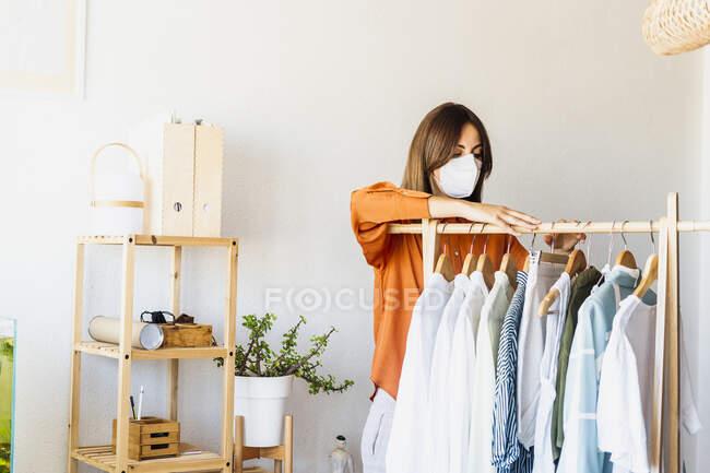 Жіночий дизайнер, який працює вдома з одягом, стоїть у захисній масці. — стокове фото