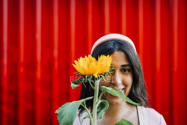 Jeune femme devant le mur rouge, oeil couverture avec tournesol — Photo de stock