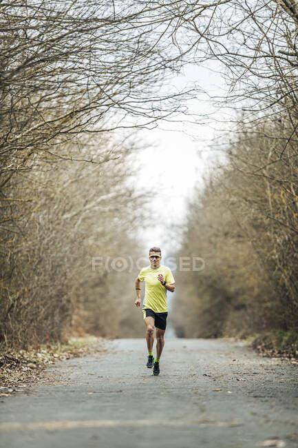 Юный спортсмен бежит по проселочной дороге среди голых деревьев — стоковое фото
