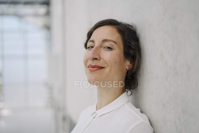Portrait of a smiling businesswoman at a concrete wall — Stock Photo