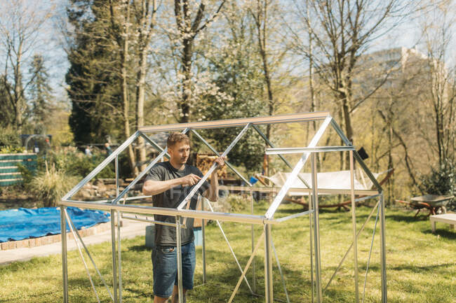 Hombre adulto medio construyendo invernadero en el patio durante el día soleado - foto de stock