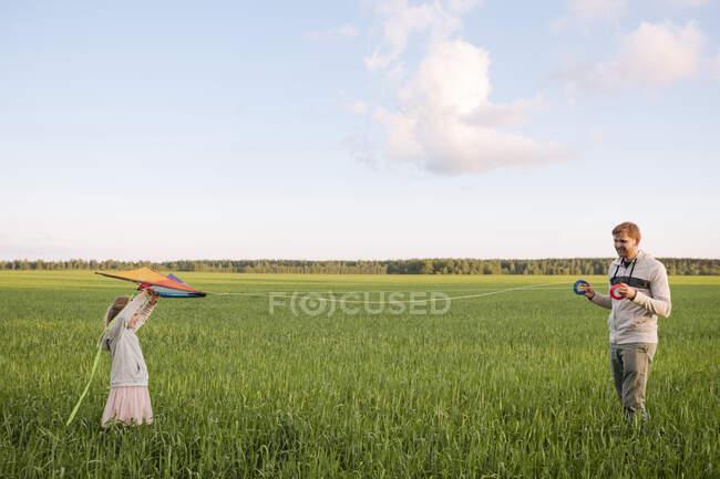 Vater hält Spulen, während Tochter Drachen über grüne Landschaft fliegt — Stockfoto