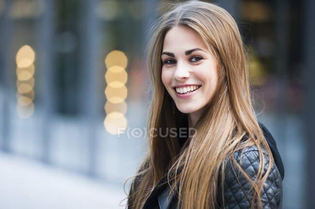 Hermosa joven con el pelo largo y castaño sonriendo al aire libre - foto de stock