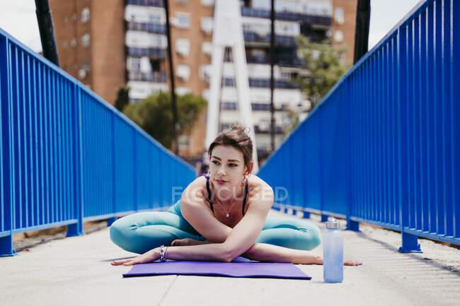 Женщина практикует йогу на мосту — стоковое фото