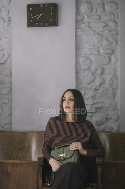 Задумчивая молодая женщина с сумочкой сидит на стуле в дизайнерской студии — стоковое фото