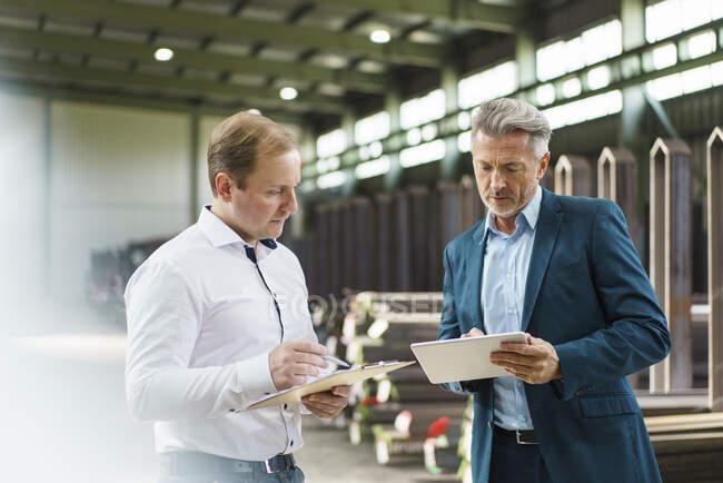 Homme d'affaires avec tablette et employé avec presse-papiers dans une usine — Photo de stock