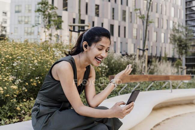 Joyeux appel vidéo femme d'affaires sur téléphone portable tout en étant assis en ville — Photo de stock