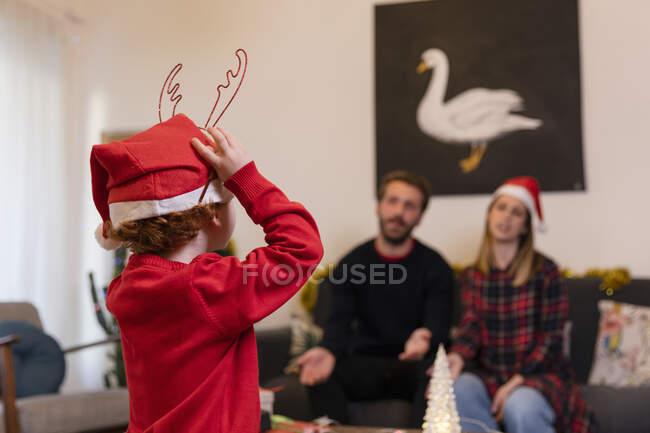 Батьки, які дивляться на сина в капелюсі Санти під час Різдва. — стокове фото