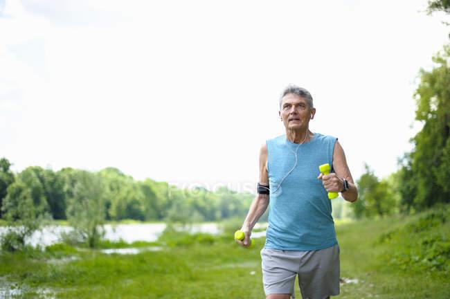 Активный старший бегун с гантелями на берегу реки против ясного неба — стоковое фото