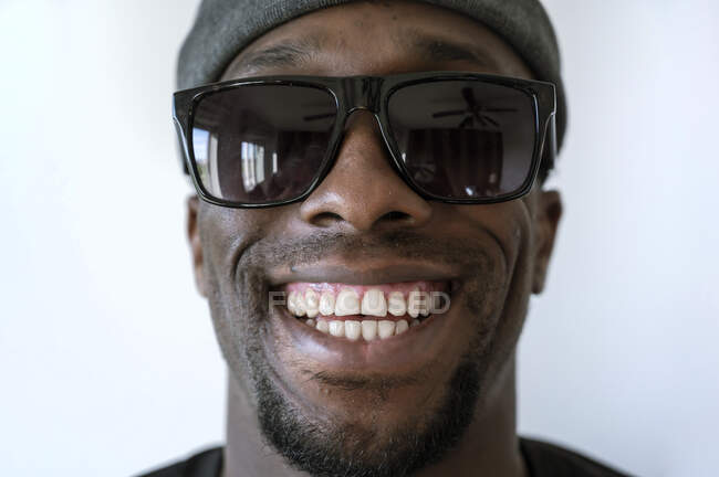 Знятий портрет усміхненого молодого чоловіка у сонцезахисних окулярах на білому тлі. — стокове фото