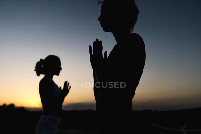Силуэт женщин в молитвенном положении на закате — стоковое фото