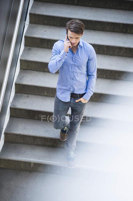 Empresario hablando por teléfono inteligente mientras se mueve hacia abajo en los pasos - foto de stock