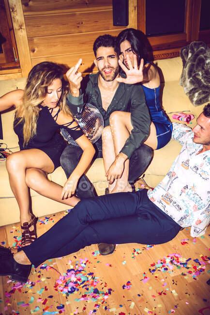 Giovane uomo e donna gesticolare mentre seduto con gli amici in festa — Foto stock