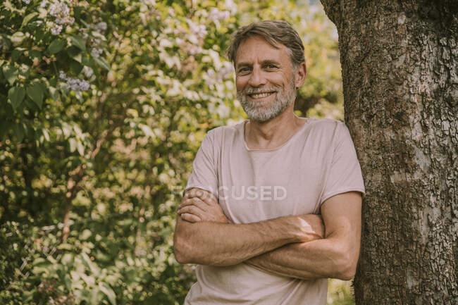 Lächelnder bärtiger Mann mit verschränkten Armen lehnt an Baumstamm im Garten — Stockfoto