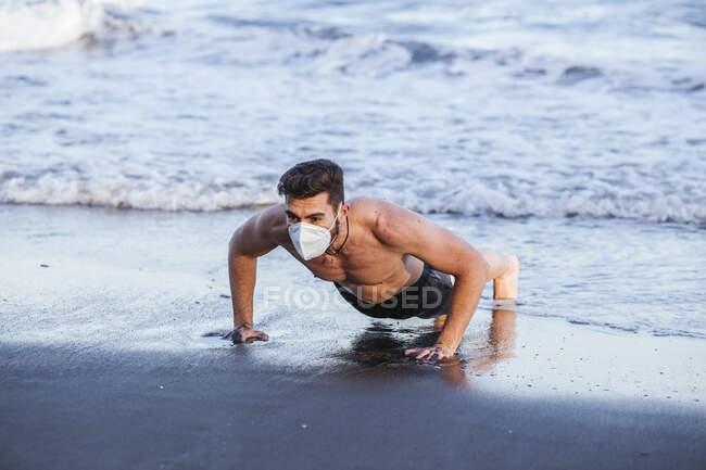 Мужчина без рубашки в маске для лица во время отжиманий на пляже на закате — стоковое фото