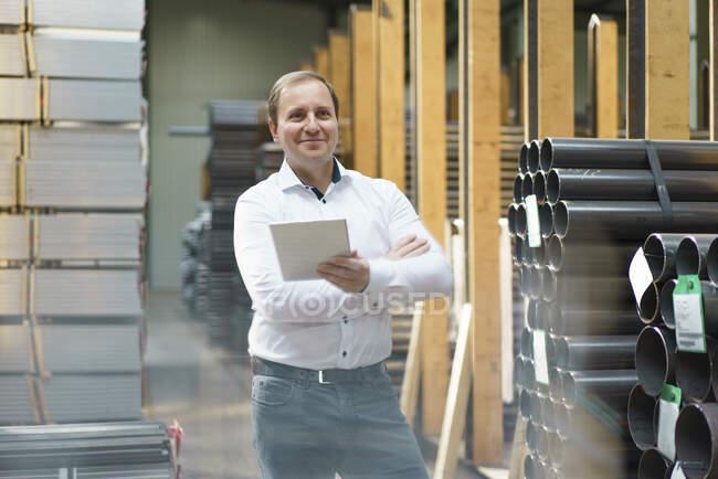 Усміхнений бізнесмен тримає планшет на фабриці. — стокове фото