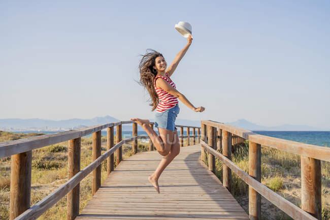 Eccitato adolescente che salta sul lungomare in spiaggia contro il cielo blu chiaro — Foto stock