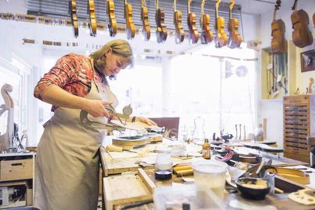 Female violin maker at work in her workshop — Stock Photo
