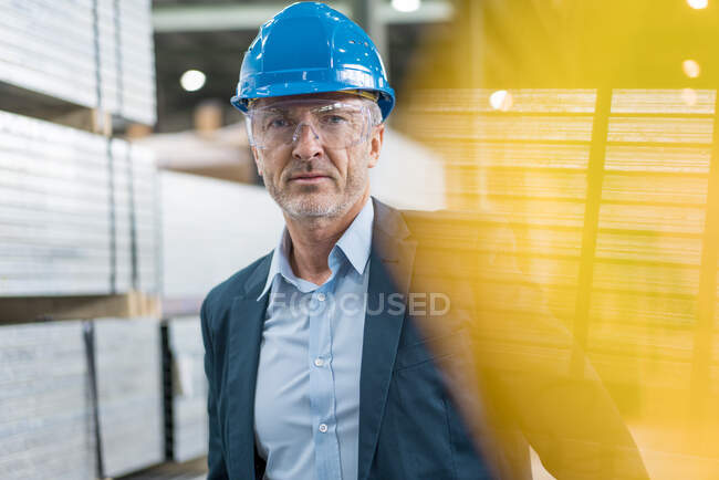 Portrait of mature businessman wearing hard hat and safety goggles in a factory — Stock Photo