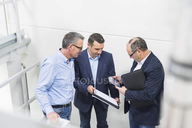 Tres hombres de negocios discutiendo en una fábrica - foto de stock