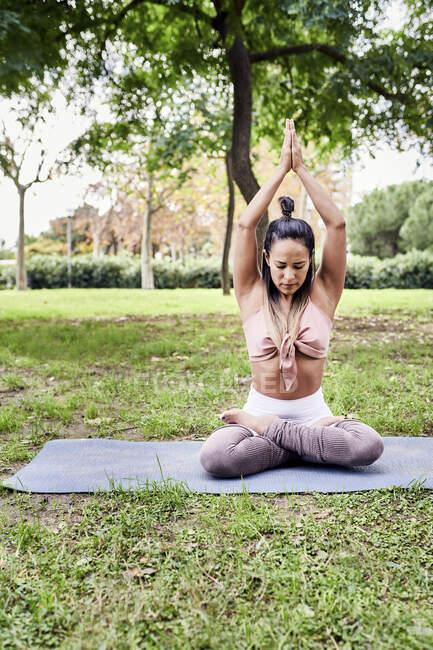 Взрослая женщина медитирует в парке — стоковое фото