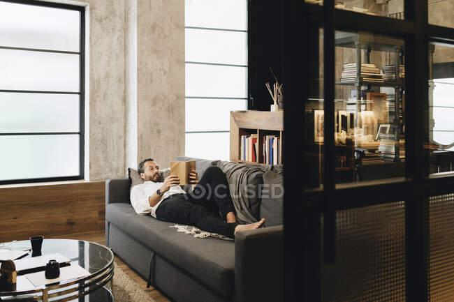 Зрелый мужчина лежит на диване, расслабляется, читает книгу — стоковое фото