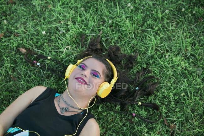 Adolescente chica con síndrome de Down usando 8s maquillaje colorido y escuchar música con auriculares amarillos - foto de stock