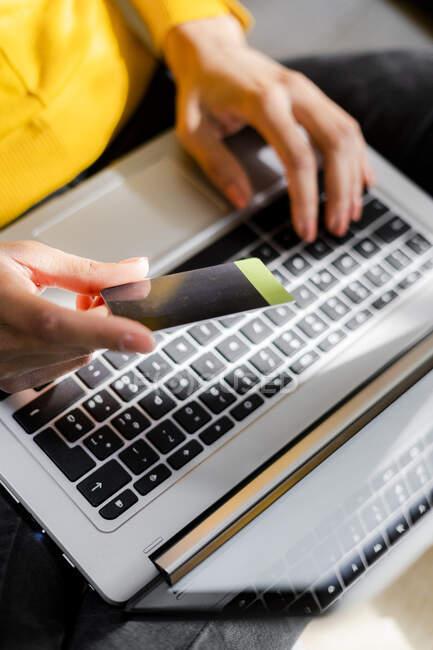 La mano de la mujer sosteniendo la tarjeta de crédito mientras usa el ordenador portátil - foto de stock