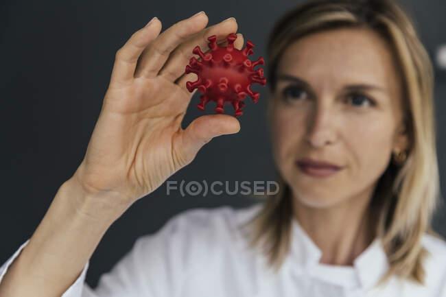 Científica mirando el modelo 3D del virus SARS-CoV-2 - foto de stock