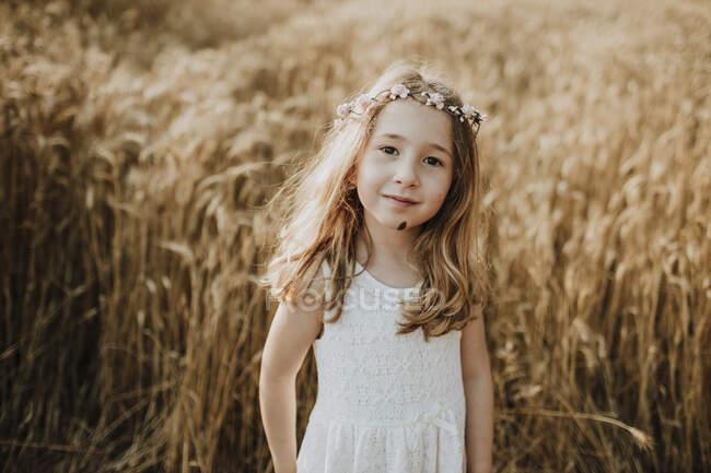 Милая блондинка, стоящая на поле из пшеницы — стоковое фото