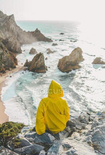 Vista posteriore della donna che indossa l'impermeabile seduta sulla roccia guardando la spiaggia, Praia da Ursa, Lisboa, Portogallo — Foto stock