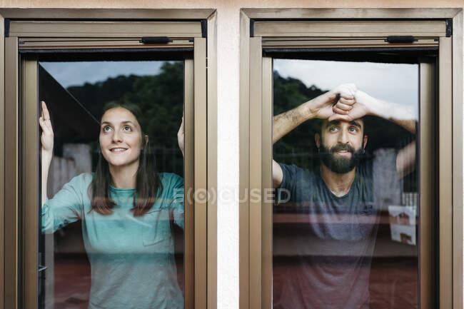 Пара смотрит в окно и думает о будущем — стоковое фото