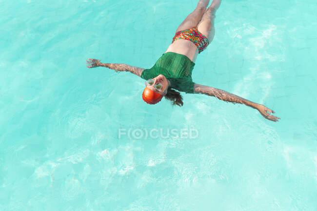 Mujer flotando en el agua en la piscina - foto de stock