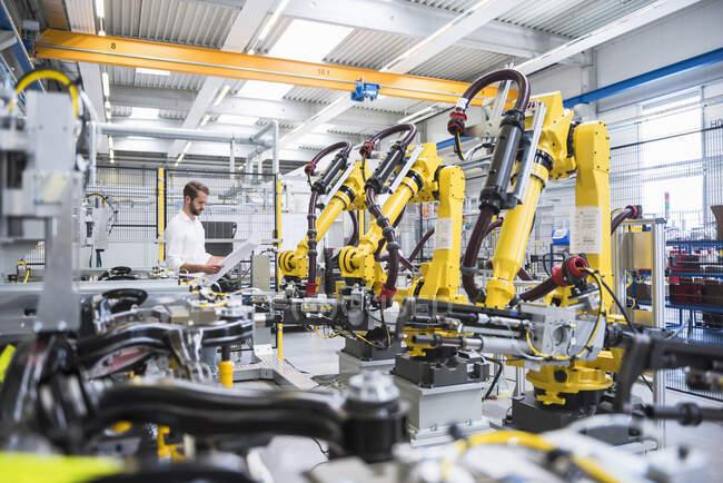 Jovem engenheiro de papel de leitura em pé por braços robóticos na indústria automatizada — Fotografia de Stock