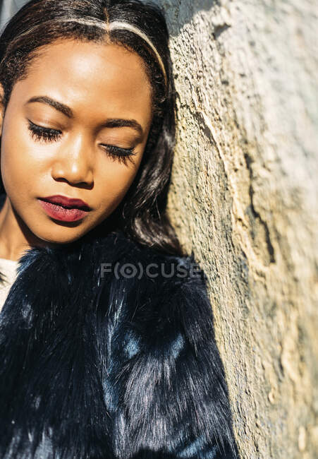 Close-up of young woman with eyes closed leaning on wall — Stock Photo