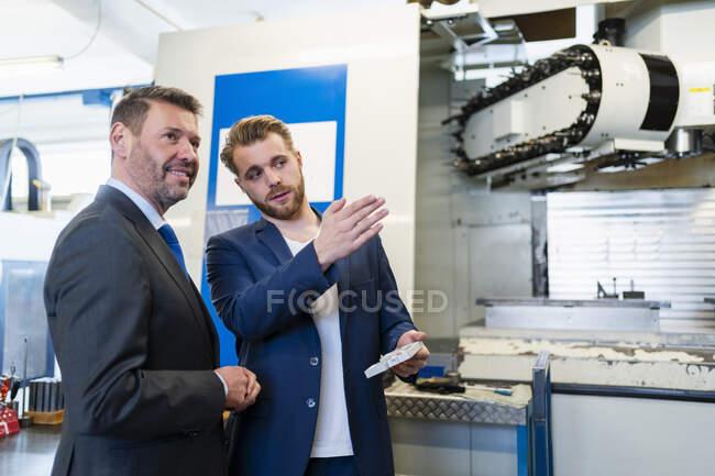 Dos hombres de negocios teniendo una reunión de trabajo en una fábrica - foto de stock