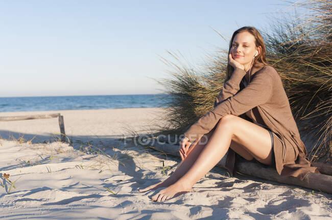 Retrato de mulher sorridente ouvindo música com fones de ouvido na praia, Sardenha, Itália — Fotografia de Stock