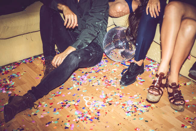 Friends sitting on sofa and floor covered in party — Stock Photo