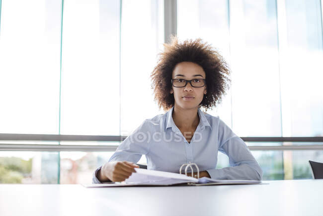 Portrait of young businesswoman sitting at table in conference room with file folder — Stock Photo