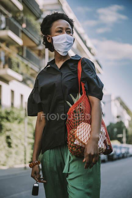Retrato de mujer joven con máscara protectora de pie en la calle con su compra - foto de stock