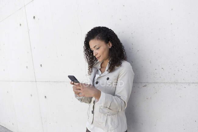 Elegante mujer de negocios usando el teléfono inteligente mientras está de pie contra la pared - foto de stock