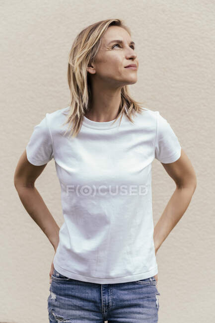 Portrait de femme blonde portant un t-shirt blanc devant un mur clair levant les yeux — Photo de stock