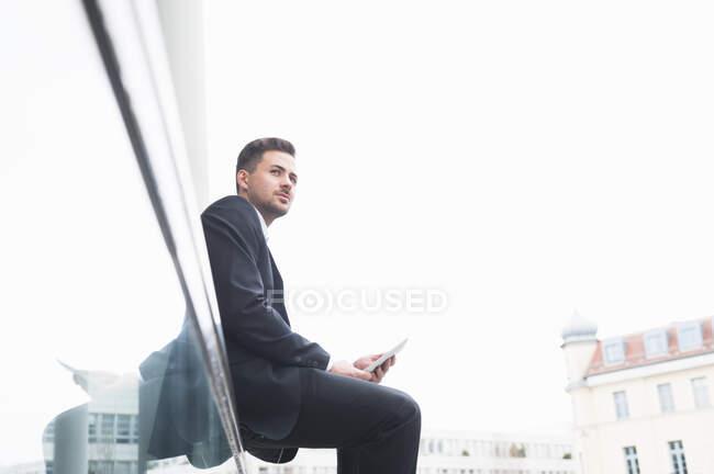 Homme d'affaires tenant tablette numérique tout en étant assis sur une rampe en verre contre le ciel clair — Photo de stock