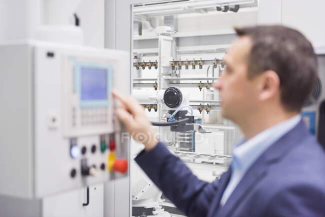 Empresário operando uma máquina em uma fábrica — Fotografia de Stock
